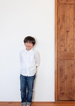 子供が壁にもたれているイメージ写真